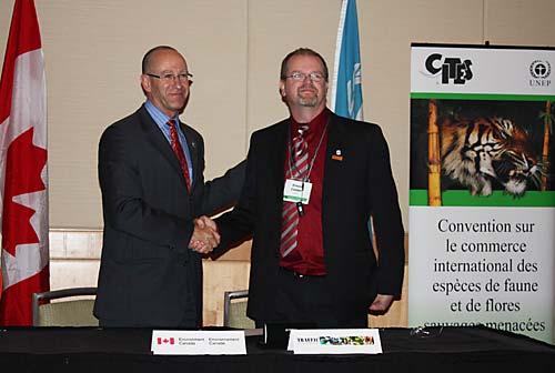 カナダ環境省の執行局の主任執行官のアルビン・トレンブレイとトラフィックノースアメリカのカナダオフィス代表のアーニー・クーパーがそれぞれの機関を代表して署名をおこなっているところ c Environment Canada